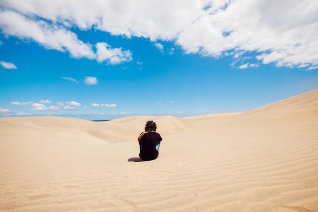 L'uomo si siede su un paesaggio di dune del deserto. uomo che fa un giro turistico tra le dune in una calda giornata estiva. Foto Premium