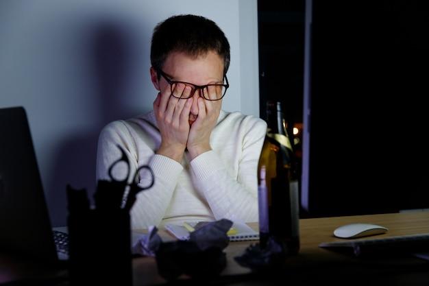 L'uomo si strofina gli occhi stanchi lavorando a tarda notte, beve una birra per rilassarsi, si addormenta per la fatica. Foto Premium