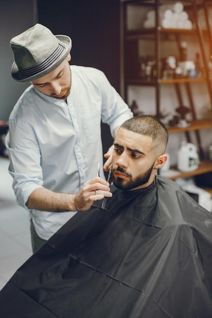 L'uomo si taglia la barba nel barbiere. Foto Gratuite