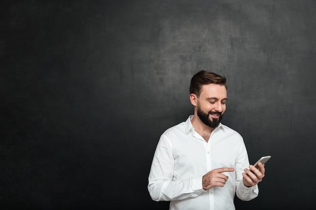 L'uomo sorridente contento nel messaggio di testo digitante della camicia bianca o lo scorrimento inserisce la rete sociale facendo uso dello smartphone sopra grigio scuro Foto Gratuite