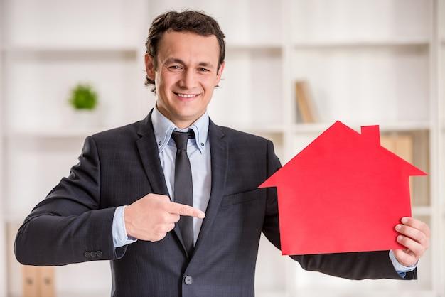 L'uomo sorridente dell'agente immobiliare sta tenendo un modello della casa. Foto Premium