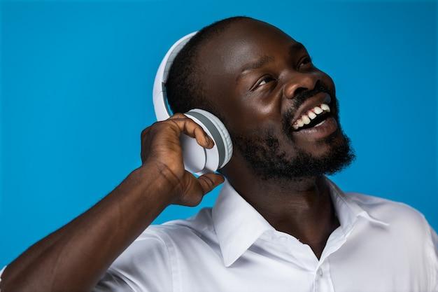L'uomo sorridente gode dell'ascolto di musica Foto Gratuite