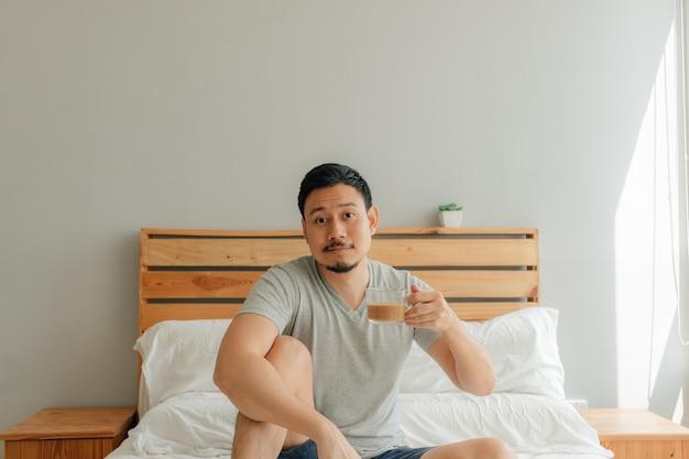 L'uomo sta bevendo una tazza di caffè sul letto nella sua camera da letto. Foto Premium