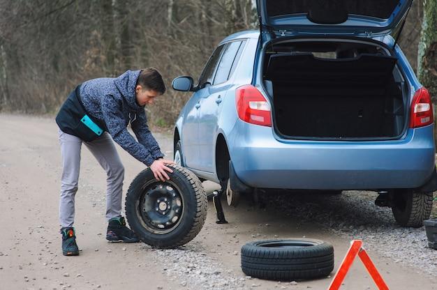 L'uomo sta cambiando la gomma con la ruota sull'auto Foto Premium