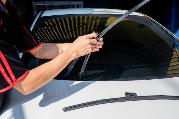 L'uomo sta cambiando tergicristalli su una macchina Foto Premium