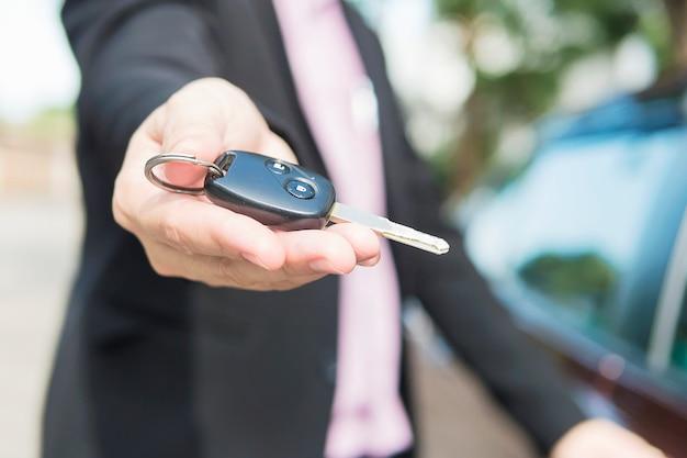 L'uomo sta dando una chiave della macchina a qualcuno Foto Gratuite