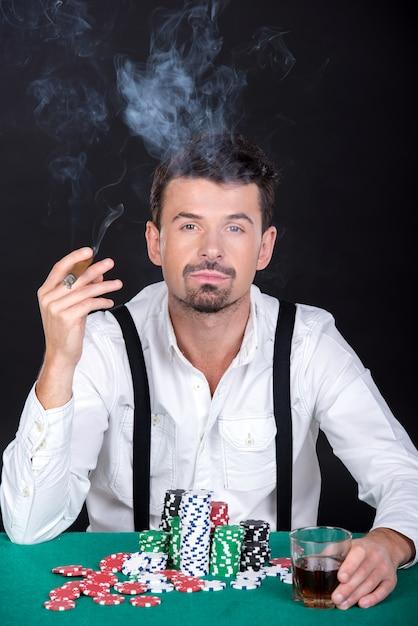 L'uomo sta giocando a poker nei casinò e fumando. Foto Premium