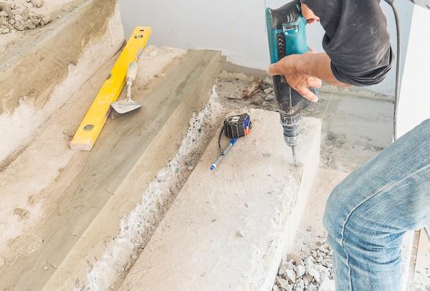 L'uomo sta lavorando con il rafforzamento della modifica della struttura delle scale in calcestruzzo usando un trapano a mano Foto Gratuite