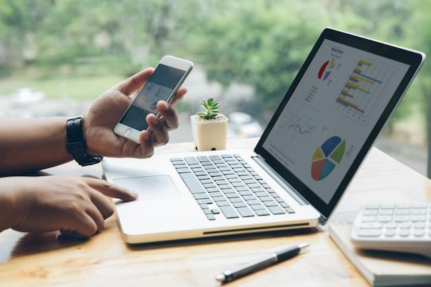 L'uomo sta lavorando con uno smartphone e un laptop nel suo ufficio Foto Premium
