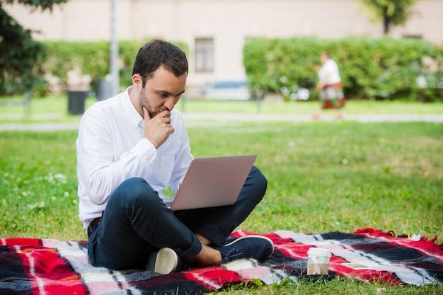 L'uomo sta lavorando utilizzando il computer portatile al parco. all'aperto, il ragazzo sembra sfidato e pensa Foto Premium