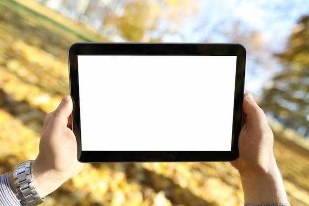 L'uomo sta nel parco di autunno ed esamina la compressa Foto Premium