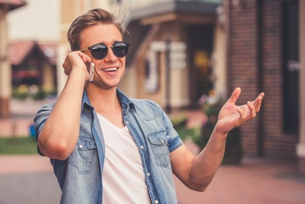 L'uomo sta parlando al telefono cellulare e sorridendo Foto Premium