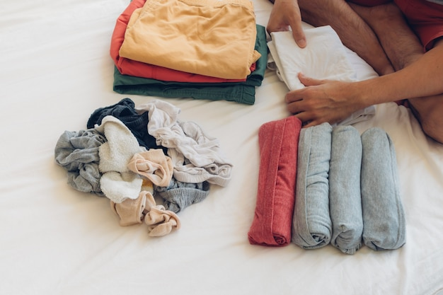 L'uomo sta piegando e sistemando i vestiti sul letto. Foto Premium