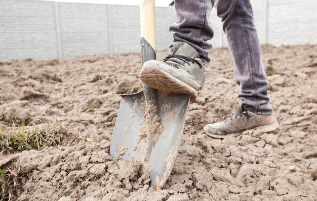 L'uomo sta scavando il terreno nella sua casa di campagna Foto Premium