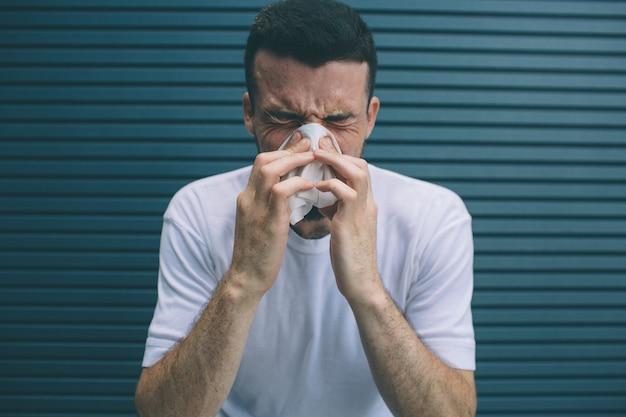 L'uomo starnutisce e copre naso e bocca con un tovagliolo. si sente male. isolato su strisce Foto Premium
