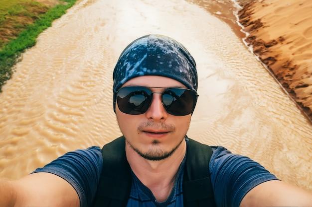 L'uomo su un'escursione con uno zaino prende un selfie sul volto della fotocamera in occhiali da sole e una bandana durante il viaggio Foto Premium
