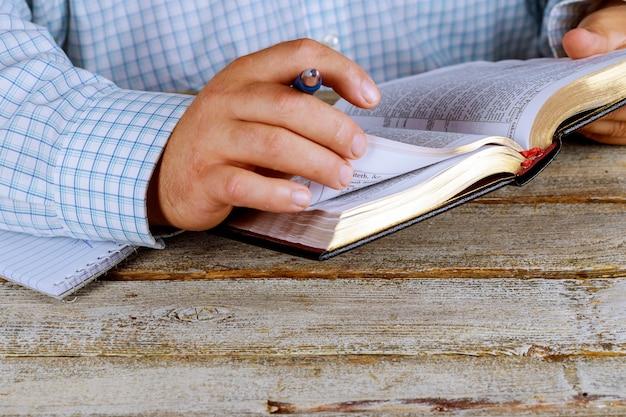 L'uomo tiene in mano una penna con una sacra bibbia aperta che giace di fronte a lui Foto Premium