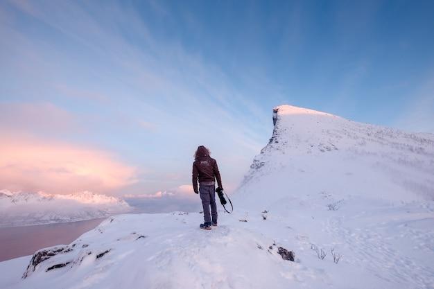 L'uomo turistico si arrampica sulla montagna nevosa superiore Foto Premium