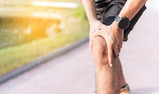 L'uomo usa le mani sul ginocchio mentre corre su strada nel parco. Foto Premium