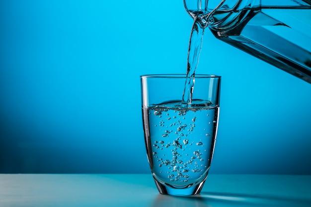 L'uomo versa l'acqua dal bicchiere Foto Premium