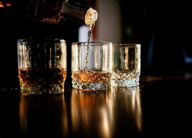 L'uomo versa whiskey negli occhiali in piedi davanti a un tavolo di legno Foto Premium