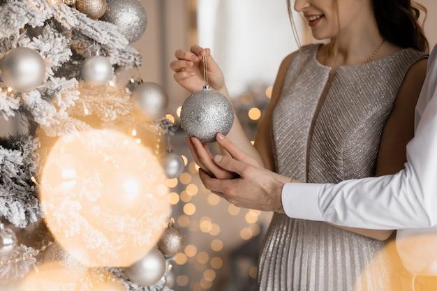 L'uomo vestito elegante e la donna in abito d'argento si abbracciano tenero in piedi davanti a un albero di natale Foto Gratuite