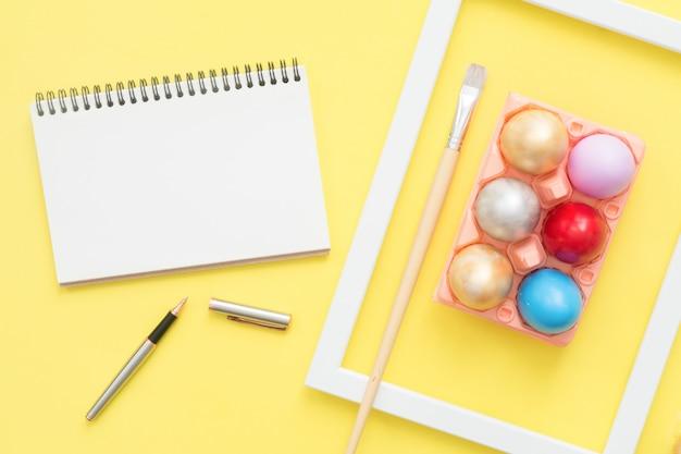 L'uovo di pasqua variopinto di vista superiore piana di disposizione dipinto in composizione in colori pastello e deride sul taccuino in bianco Foto Gratuite