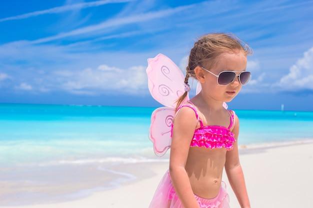 La bambina adorabile con le ali gradisce la farfalla sulla vacanza della spiaggia Foto Premium