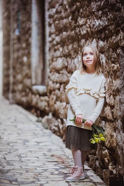 La bambina adorabile nella tendenza copre la condizione nella vecchia città nel giorno di molla soleggiato con i fiori gialli Foto Premium