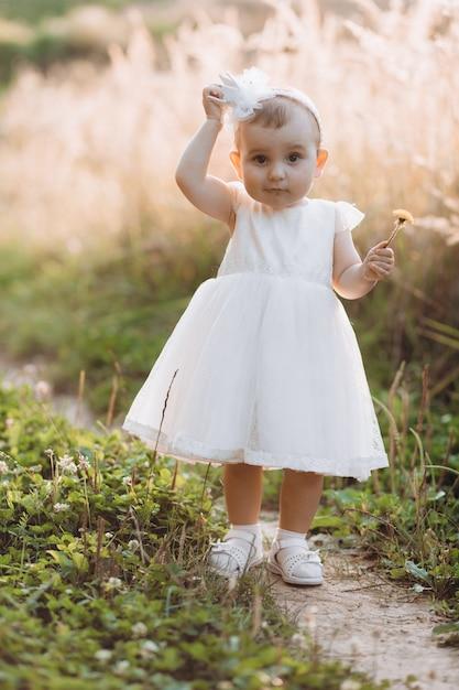 La bambina affascinante in vestito bianco cammina lungo il percorso nel campo Foto Gratuite