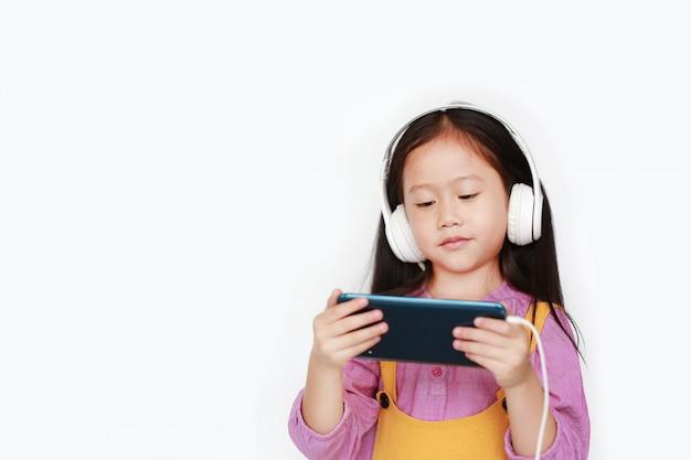 La bambina asiatica gode della musica d'ascolto con le cuffie Foto Premium
