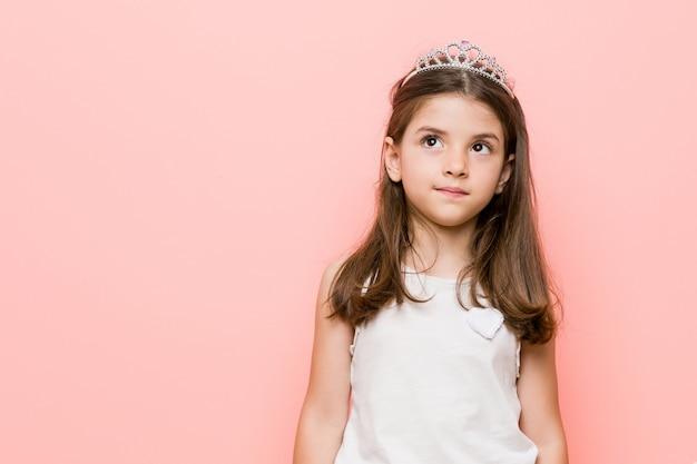 La bambina che indossa una principessa sembra sognare di raggiungere obiettivi e scopi Foto Premium
