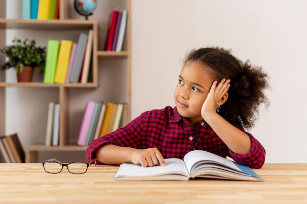 La bambina che pensa al libro ha letto Foto Gratuite