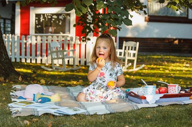 La bambina che si siede sull'erba verde Foto Gratuite