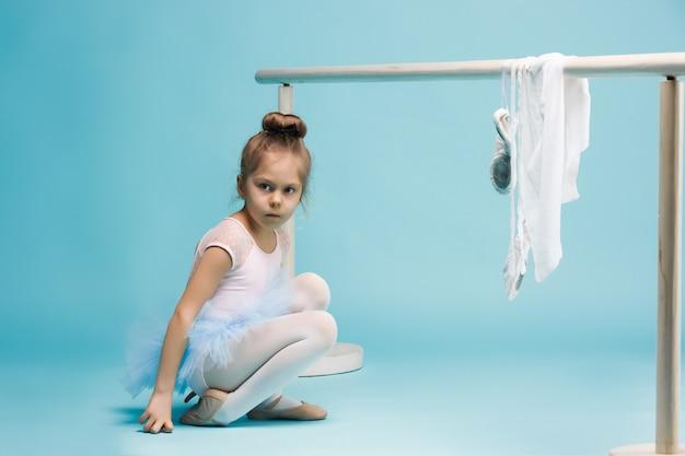 La bambina come ballerina della ballerina che posa vicino allo scaffale di balletto sullo studio blu Foto Gratuite