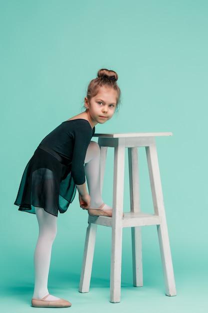 La bambina come ballerina della ballerina vicino alla sedia sullo studio blu Foto Gratuite