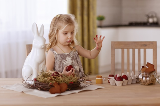 La bambina dipinge le uova di pasqua nella stanza alla tavola di festa. Foto Premium