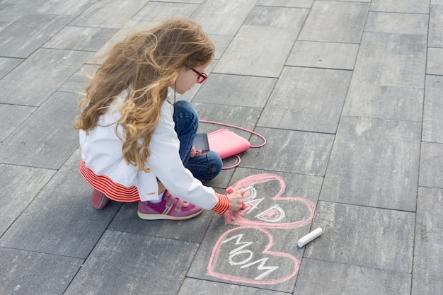 La bambina disegna il testo di mamma e papà a forma di cuore Foto Premium