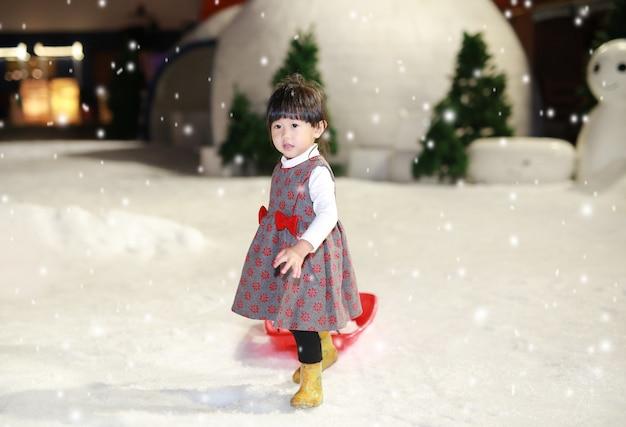 La bambina felice che porta una giacca rosso-grigia ha un divertimento in neve, orario invernale. Foto Premium