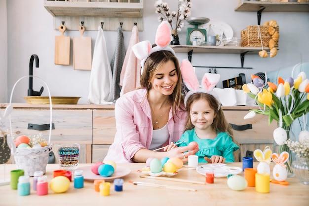 La bambina felice con la madre che dipinge le uova per pasqua Foto Gratuite
