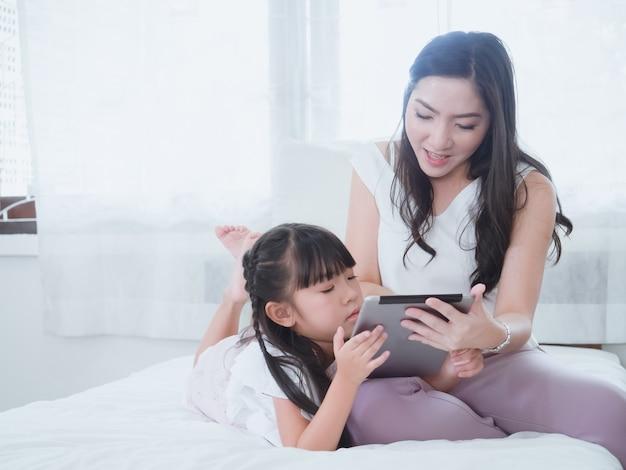 La bambina gioca a letto con sua madre Foto Premium