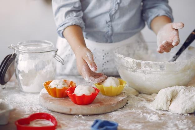 La bambina in un cappello bianco dello shef cucina l'impasto per i biscotti Foto Gratuite