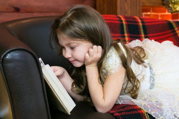La bambina legge un libro con interesse. Foto Premium