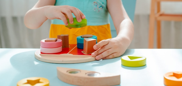 La bambina raccoglie il selezionatore multicolore di legno giocattoli per bambini di legno naturali sicuri Foto Premium