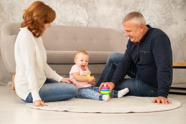 La bambina raccoglie una piramide con i nonni in salotto. la famiglia trascorre del tempo insieme indoor, livestile Foto Premium