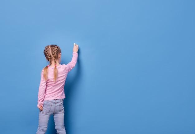 La bambina scrive con il gesso su sfondo blu Foto Premium