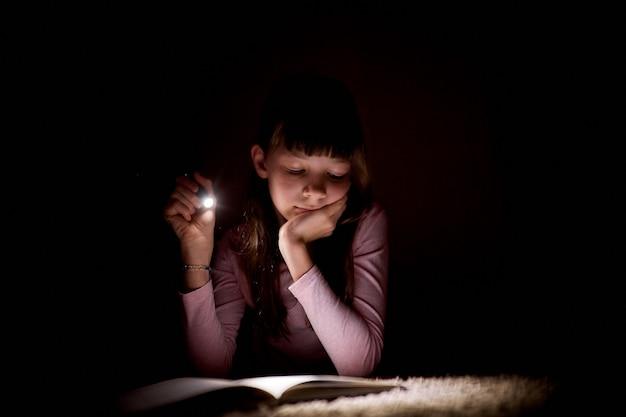 La bambina sta leggendo un libro con una torcia elettrica in una stanza buia di notte. Foto Premium
