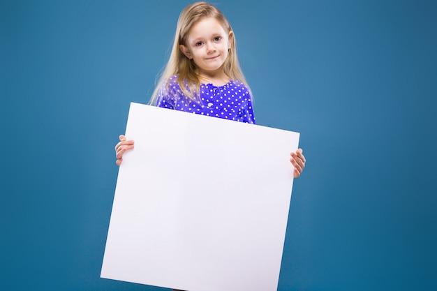 La bambina sveglia in vestito viola tiene il cartello in bianco vuoto Foto Premium