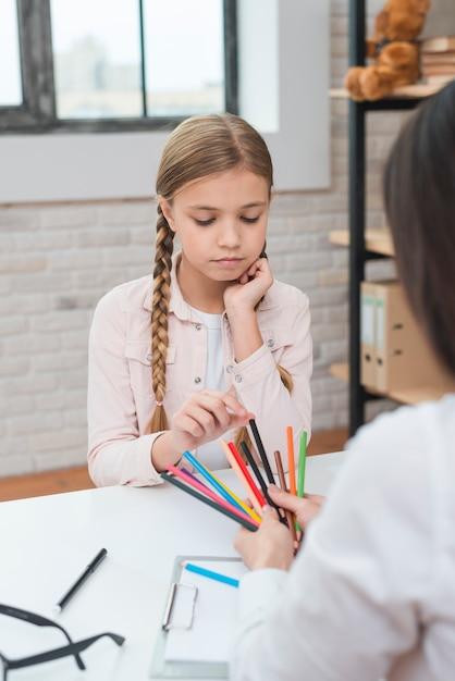 La bambina triste che sceglie le matite colorate tiene dallo psicologo femminile Foto Gratuite