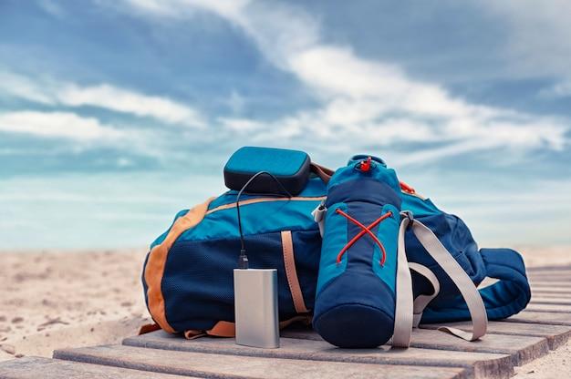 La banca di potere carica un altoparlante musicale sullo sfondo di borse da viaggio in spiaggia in una giornata nuvolosa Foto Premium